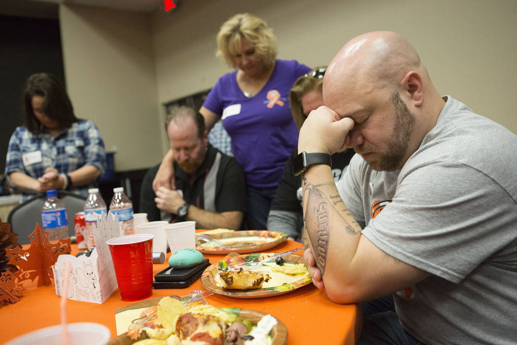 Lee Dorchak, right, lowers his head for a prayer during a Thanksgiving dinner for Route 91 Harvest festival survivors at the Henderson Convention Center in Henderson, Saturday, Nov. 25, 2017. Brid ...