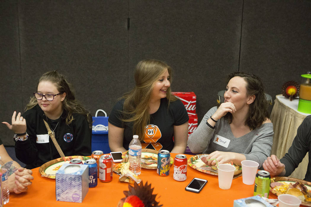 Priscilla Solorzano, left, Lisa Stadtmiller, and Tersa Peiffer talk during a Thanksgiving dinner for Route 91 Harvest festival survivors at the Henderson Convention Center in Henderson, Saturday,  ...