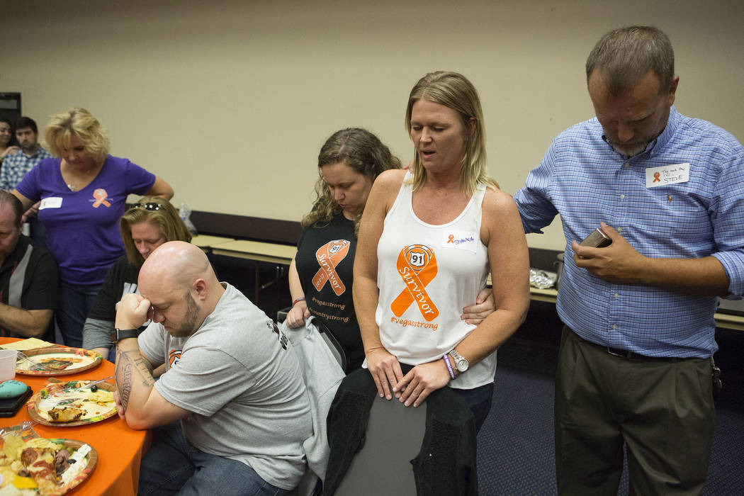 One of the dinner's organizers Shawna Bartlett, second from right, leads a prayer during a Thanksgiving dinner for Route 91 Harvest festival survivors at the Henderson Convention Center in Henders ...