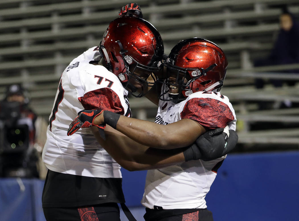 San Diego State running back Rashaad Penny, right, celebrates his rushing touchdown with Ryan Pope (77) during the second half of an NCAA college football game against San Jose State on Saturday,  ...