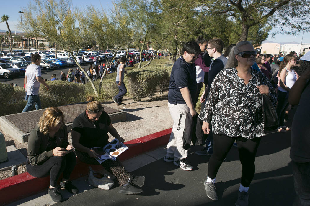 Jazmin Garcia, left, and Susana Castillo page though an ad while they wait in line to enter JCPenney for Thanksgiving Day shopping at the at the Galleria at Sunset wraps around the parking lot in  ...