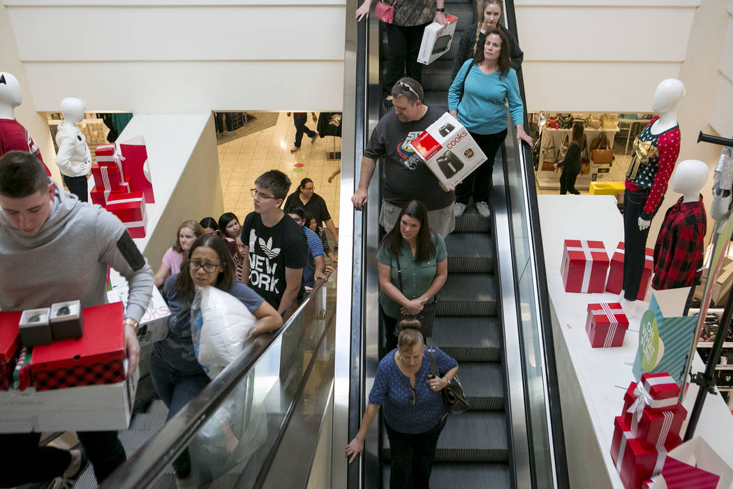 Shoppers travel up and down the escalator with their Thanksgiving Day shopping finds at the JCPenney at the Galleria at Sunset in Henderson, Thursday, Nov. 23, 2017. Bridget Bennett Las Vegas Revi ...