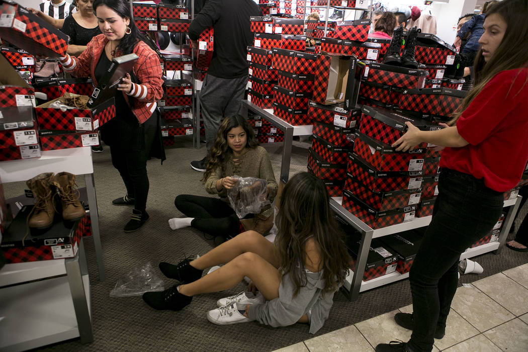 Sarah Peralta, left, and April Cinco sit on the ground as they try on shoes during Thanksgiving Day shopping at the JCPenney at the Galleria at Sunset in Henderson, Thursday, Nov. 23, 2017. Bridge ...