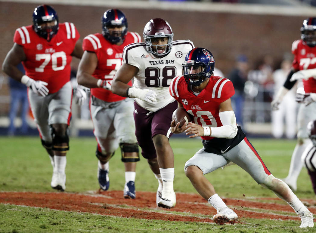 Mississippi quarterback Jordan Ta'amu (10) is pursued by Texas A&M defensive lineman Kingsley Keke (88) after outrunning his offensive line during the second half of an NCAA college football g ...