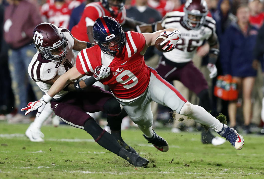 Mississippi wide receiver Tre Nixon (4) is tackled by Texas A&M defensive back Derrick Tucker (4) during the first half of an NCAA college football game in Oxford, Miss., Saturday, Nov. 18, 20 ...