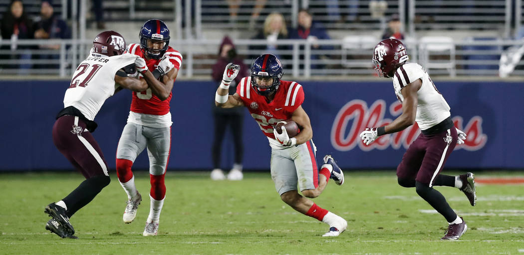 Mississippi running back Jordan Wilkins (22) runs past Texas A&M defenders during the first half of an NCAA college football game in Oxford, Miss., Saturday, Nov. 18, 2017. Texas A&M won 3 ...