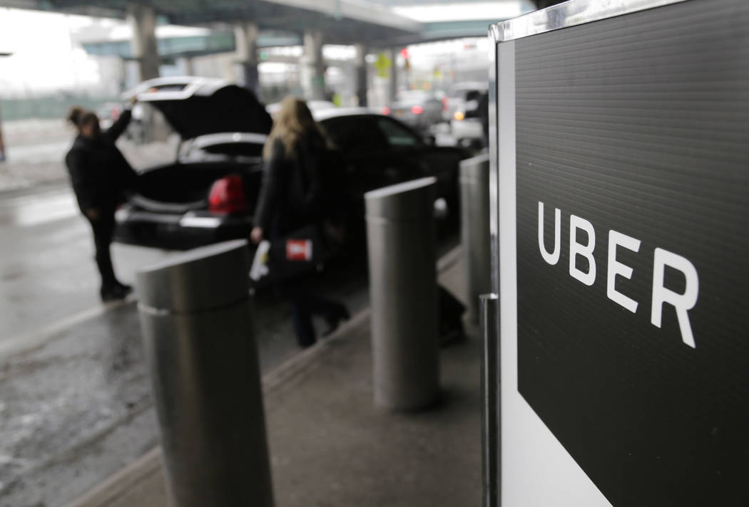 In this March 15, 2017, file photo, a sign marks a pick-up point for the Uber car service at LaGuardia Airport in New York. Uber is coming clean about its cover-up of a year-old hacking attack tha ...