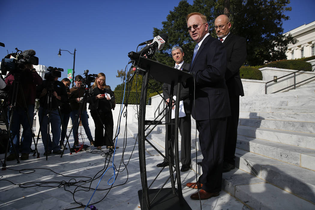 Stan Cooke, center, a member of former Alabama Chief Justice and U.S. Senate candidate Roy Moore's campaign, speaks at a news conference, Tuesday, Nov. 21, 2017, in Montgomery, Ala. (AP Photo/Bryn ...