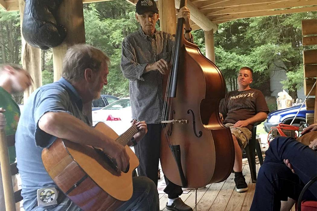 Mike Baughman, center, plays the bass with Sam Gibson, left, on guitar while Ryan Baughman, right, looks on at a cabin ON Oct. 12, 2017 in Herald, W.Va. Mike Baughman is fighting a rare bile duct  ...