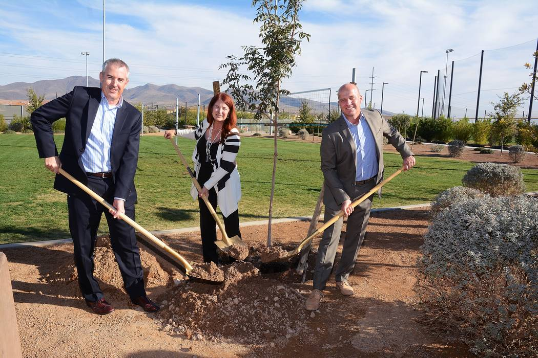 City of Henderson Director of Public Works, Parks and Recreation Robert Herr, left, Mayor Debra March, center, and Pardee Homes Nevada Division President Klif Andrews join in planting a Chinese re ...
