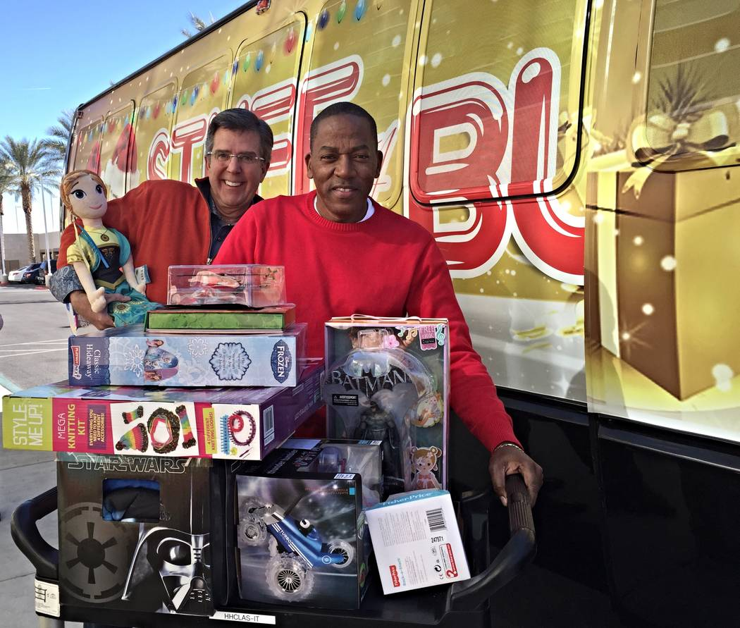 Last year, Tom Warden of The Howard Hughes Corp., left, helped Clark County Commissioner Lawrence Weekly load toys into a bus for an effort that benefits children in foster care. This year, the co ...