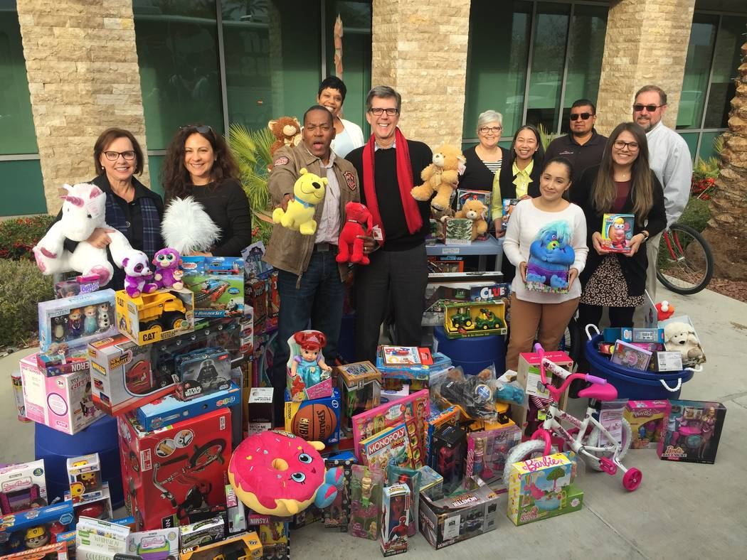 """Tom Warden of The Howard Hughes Corp. and Clark County Commissioner Lawrence Weekly, center, help gather toys for the annual """"Joys of Christmas,"""" the fifth annual toy drive. (Summerlin)"""