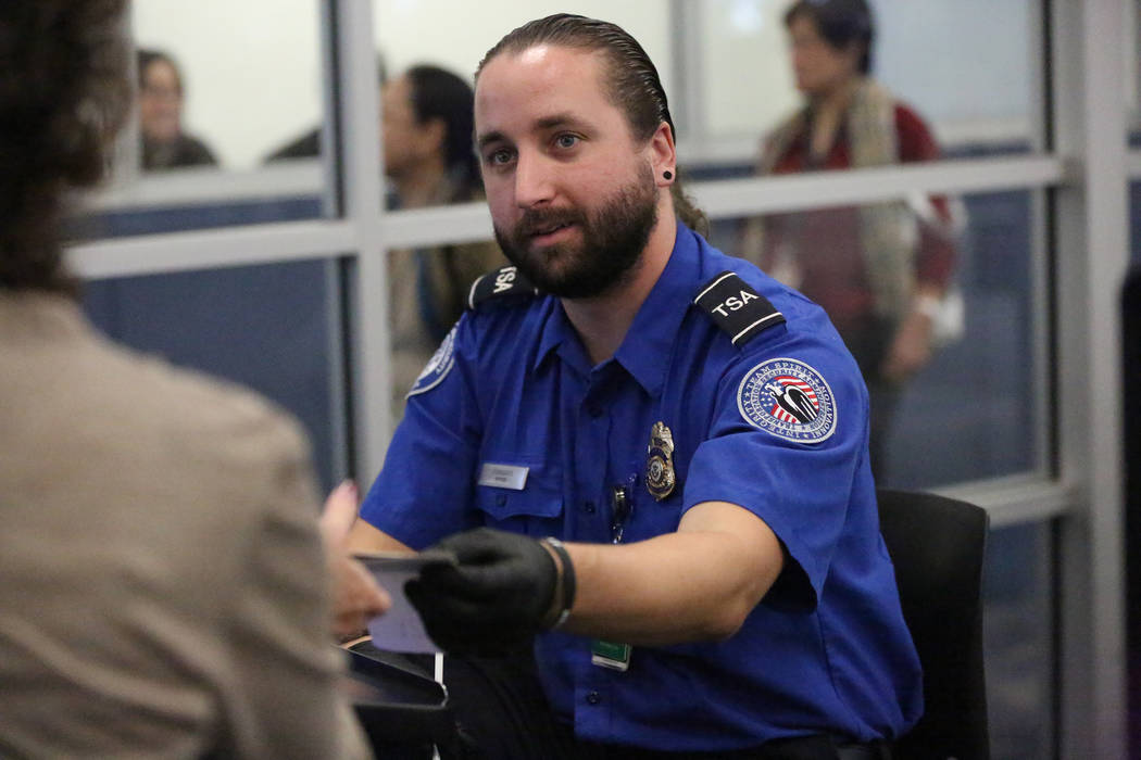 transportation security officer alejandro fornaris verifies passenger identification at a mccarran international airport security check point