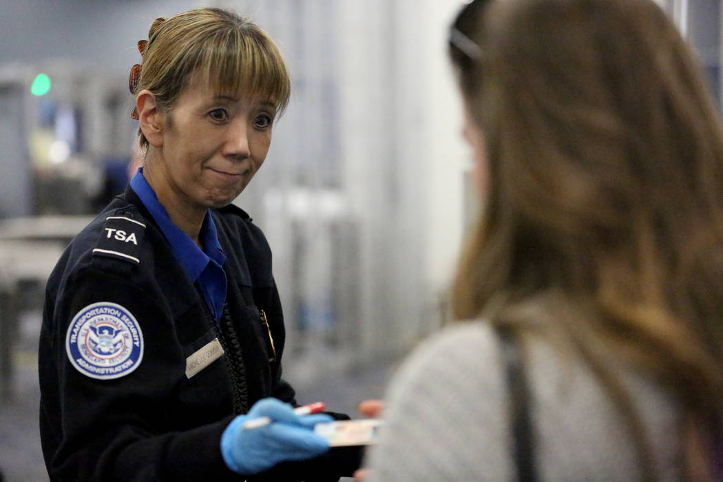 Transportation Security Officer Michelle Gerolaga verifies passenger identification at a McCarran International Airport security check point on the day before Thanksgiving, Wednesday, Nov. 22, 201 ...