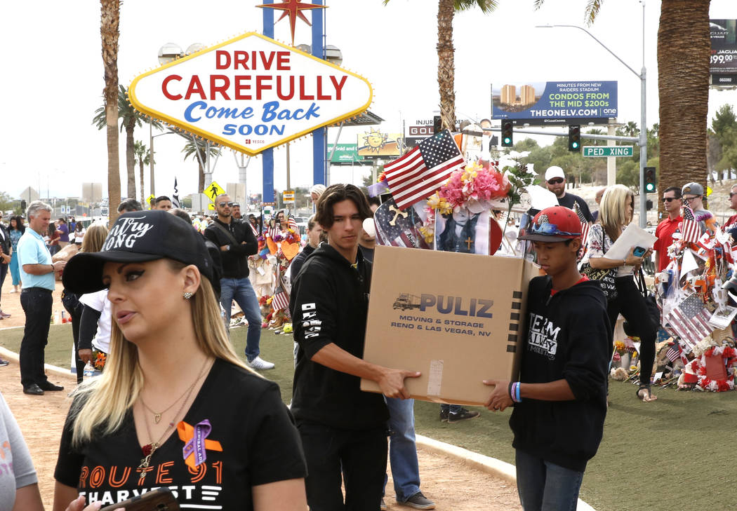 Matthew Ferandell, center, cousin of Angela Gomez, Oct. 1 shooting victim, and Ben Riccardi, right, carry boxed up cross and items from the Route 91 Harvest memorial at the Welcome to Fabulous Las ...