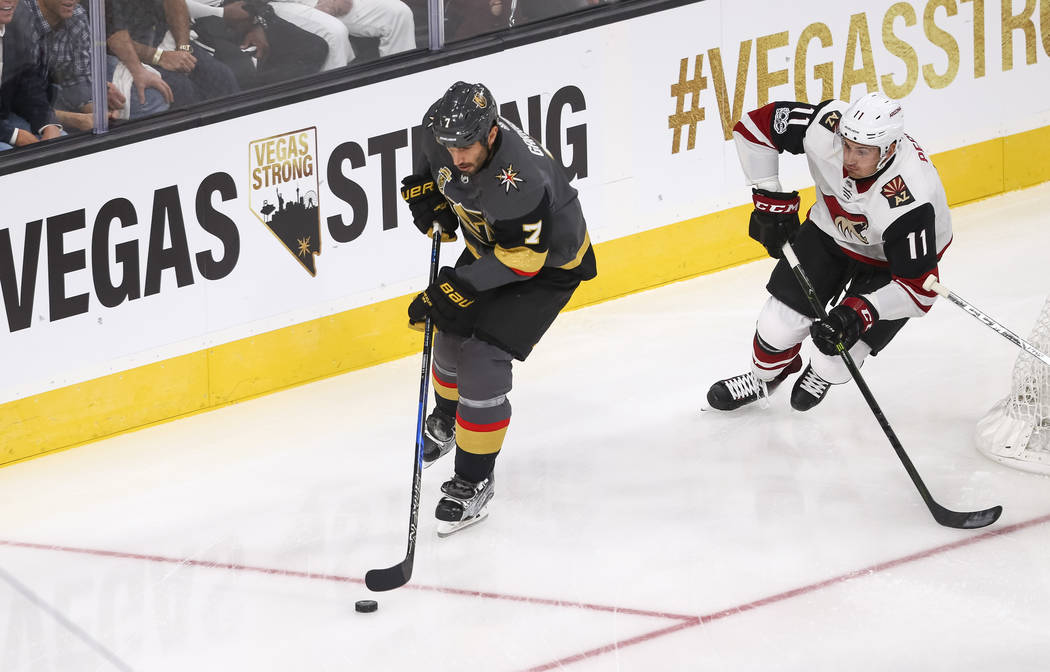 Vegas Golden Knights defenseman Jason Garrison (7) gains control of the puck as he is trailed by Arizona Coyotes left wing Brendan Perlini (11) during the first period of an NHL hockey game betwee ...