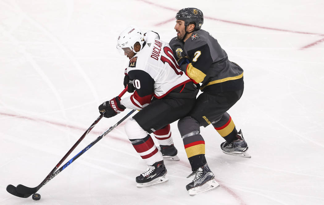 Vegas Golden Knights defenseman Jason Garrison (7) puts pressure on Arizona Coyotes left wing Anthony Duclair (10) during the first period of an NHL hockey game between the Vegas Golden Knights an ...