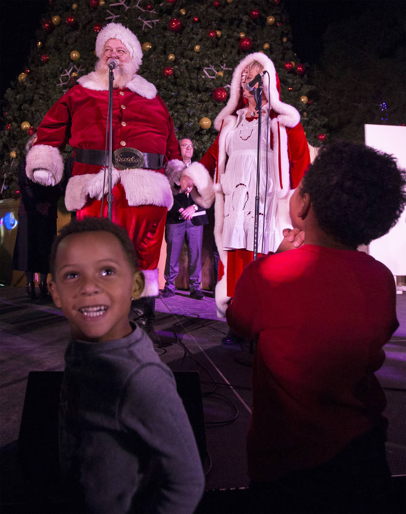 Santa and Mrs. Claus sing a song to the crowd as Madden Flaathen, left/front, smiles with excitement at Opportunity Village's Magical Forest on Friday, Nov. 24, 2017, in Las Vegas. Benjamin Hager  ...