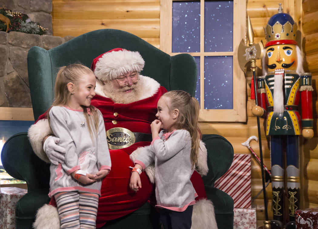 Santa listens to toy requests from Selena Dexter, left, and sister Sophie at Opportunity Village's Magical Forest on Friday, Nov. 24, 2017, in Las Vegas. Benjamin Hager Las Vegas Review-Journal @b ...