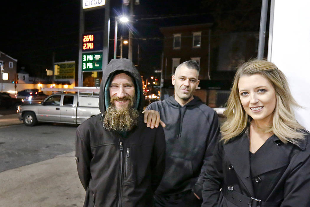 In this Nov. 17, 2017 photo, Johnny Bobbitt Jr., left, Kate McClure, right, and McClure's boyfriend Mark D'Amico pose at a CITGO station in Philadelphia. When McClure ran out of gas, Bobbitt, who  ...