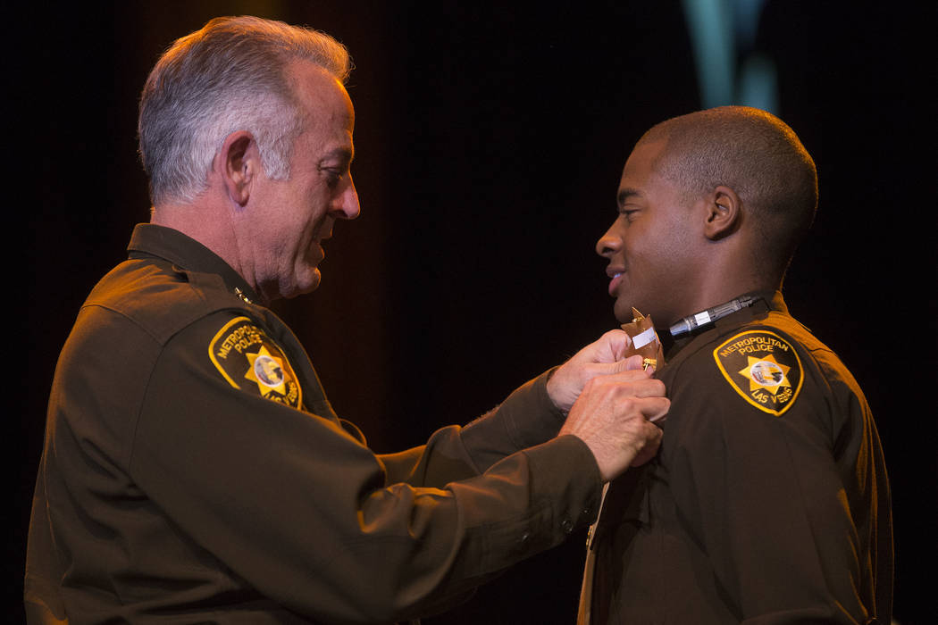Sheriff Joe Lombardo, left, presents new graduate Donte' Bastiste with his badge during a Las Vegas Metropolitan Police Department graduation ceremony at The Orleans hotel-casino in Las Vegas, Wed ...