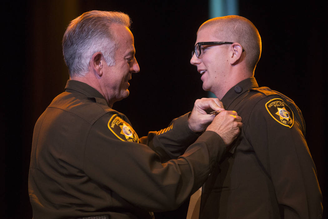 Sheriff Joe Lombardo, left, presents Zackery Bell-Brandz with his badge during a Las Vegas Metropolitan Police Department graduation ceremony at The Orleans hotel-casino in Las Vegas, Wednesday, N ...