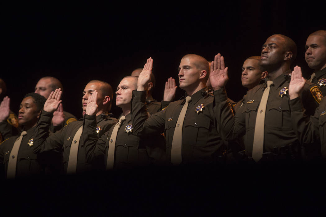 New graduates raise their hands for their oath of office and the law enforcement code of honor during a Las Vegas Metropolitan Police Department graduation ceremony at The Orleans in Las Vegas, We ...