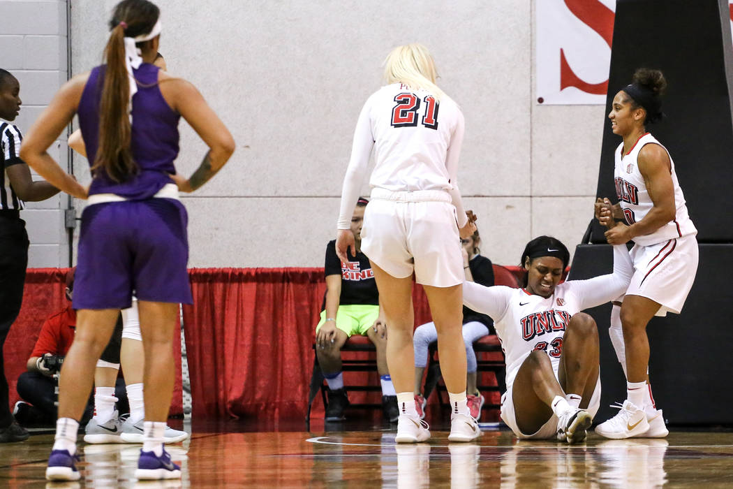 UNLV Lady Rebels forward Jordyn Bell (23), second from right, is picked up by teammates after hitting the ground during second quarter of a basketball game against the Grand Canyon Antelopes at Co ...