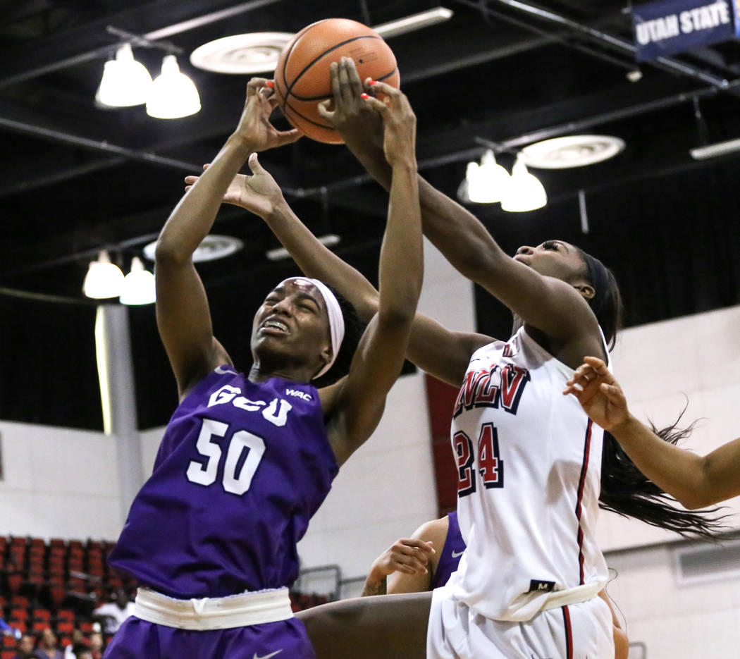 Grand Canyon Antelopes' Myra Williams (50), left, and UNLV Lady Rebels' Rodjanae Wade (24), center, jump for the ball during second quarter of a basketball game at Cox Pavilion in Las Vegas, S ...