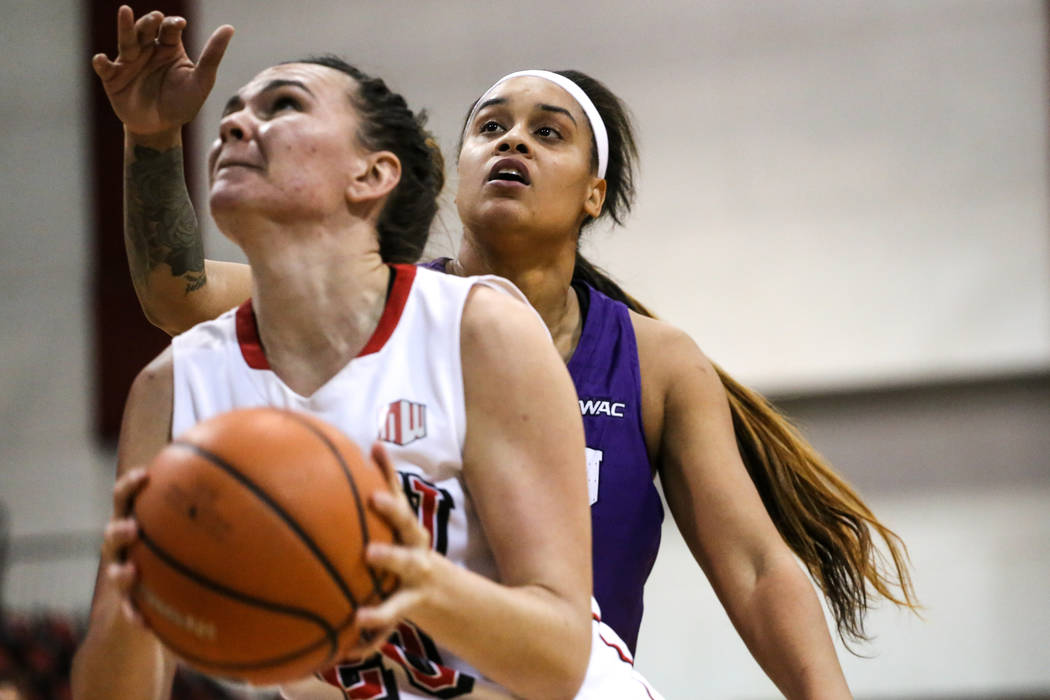 UNLV Lady Rebels forward Alyssa Anderson (20), left, is guarded by Grand Canyon Antelopes guard Jordan Jackson (3), right, during fourth quarter of a basketball game at Cox Pavilion in Las Vegas,  ...