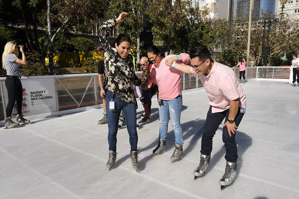 Visitors enjoy the warm weather as they attempt to stay upright wile trying to ice skate around the Holiday Ice Rink in Pershing Square in downtown Los Angeles on Wednesday, Nov. 22, 2017. (AP Pho ...