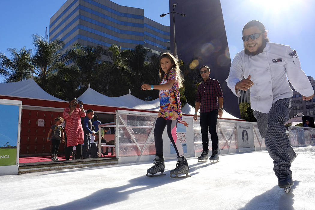 Visitors enjoy the warm weather as they ice skate around the Holiday Ice Rink in Pershing Square in downtown Los Angeles on Wednesday, Nov. 22, 2017. (AP Photo/Richard Vogel)