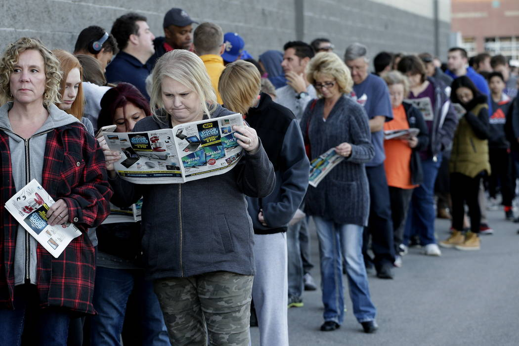 People wait in line for a Best Buy store to open for a Black Friday sale on Thanksgiving Day, Thursday, Nov. 23, 2017, in Overland Park, Kan. (AP Photo/Charlie Riedel)