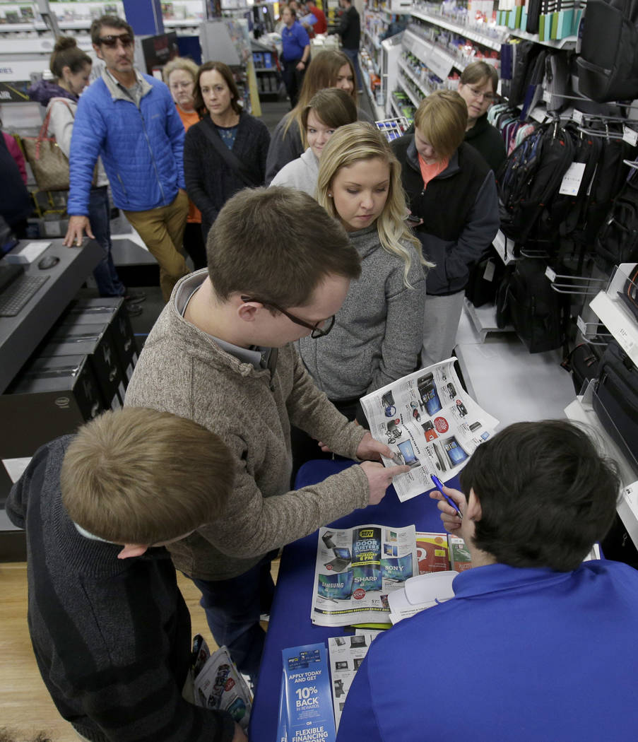 People wait in line to purchase electronics during Black Friday sale at a Best Buy store on Thanksgiving Day, Thursday, Nov. 23, 2017, in Overland Park, Kan.  (AP Photo/Charlie Riedel)