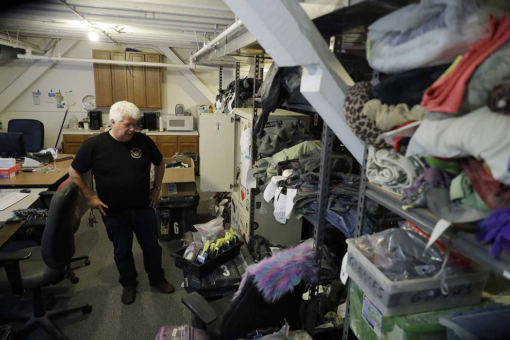In this Tuesday, Nov. 21, 2017 photo, Terry Schoop, community services department manager for Burning Man festival, looks through some lost and found items at the organization's headquarters in Sa ...