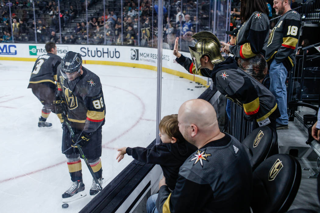 Ethan Fisher of Henderson, 12, top right, hits the glass in an attempt to get the attention of Vegas Golden Knights defenseman Nate Schmidt (88), left, before the start of a hockey game against th ...