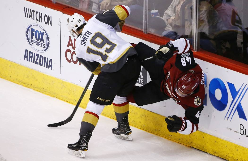 Vegas Golden Knights right wing Reilly Smith (19) checks Arizona Coyotes left wing Jordan Martinook (48) into the boards during the first period of an NHL hockey game Saturday, Nov. 25, 2017, in G ...