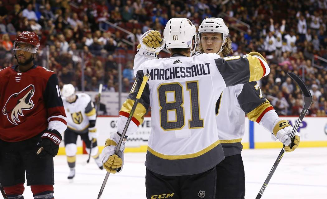 Vegas Golden Knights center William Karlsson, right, celebrates his goal against the Arizona Coyotes with Golden Knights' Jonathan Marchessault (81) as Coyotes' Anthony Duclair, left, pauses on th ...