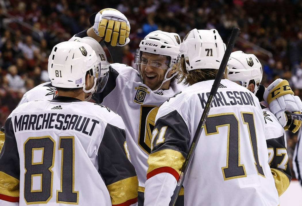 Vegas Golden Knights center William Karlsson (71) celebrates his goal against the Arizona Coyotes with defenseman Colin Miller, middle, and Jonathan Marchessault (81) during the second period of a ...