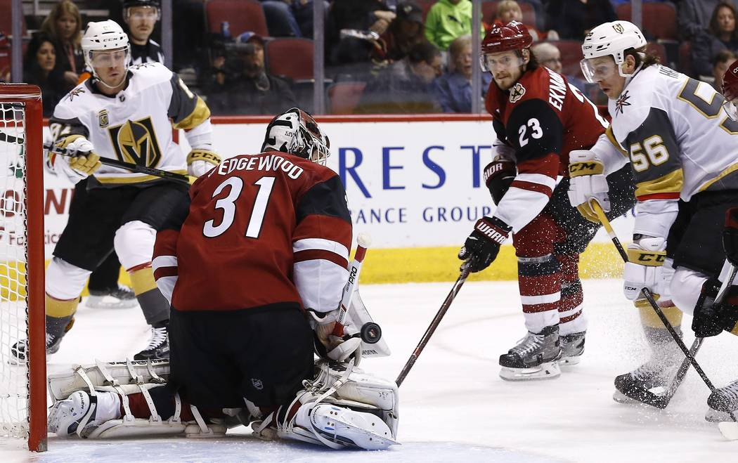 Vegas Golden Knights left wing Erik Haula (56) sends the puck past Arizona Coyotes goalie Scott Wedgewood (31) for a goal as Coyotes defenseman Oliver Ekman-Larsson (23) and Golden Knights center  ...