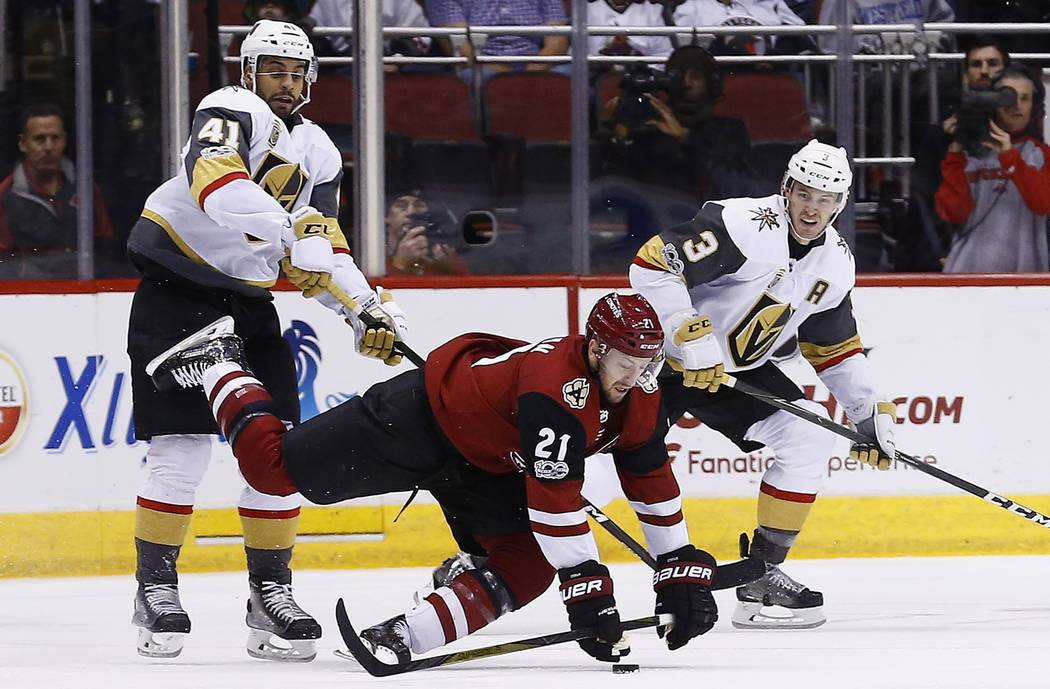 Arizona Coyotes center Derek Stepan (21) gets tripped up by Vegas Golden Knights left wing Pierre-Edouard Bellemare (41) as Golden Knights defenseman Brayden McNabb (3) looks on during the second  ...