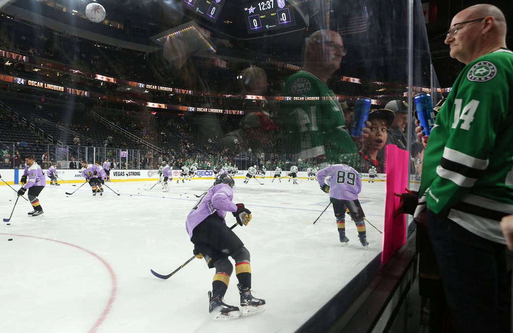 Fans watch Vegas Golden Knights players warm up in their lavender jersey in  support of the 62f15c927