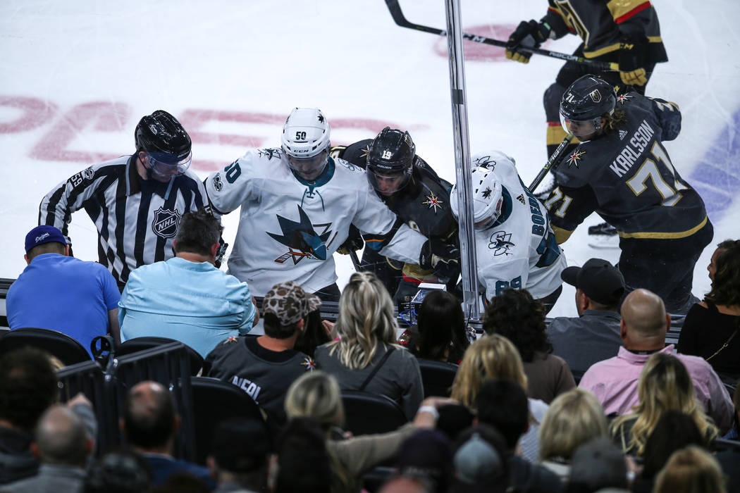 San Jose Sharks center Chris Tierney (50), left, Vegas Golden Knights right wing Reilly Smith (19), center, and San Jose Sharks left wing Mikkel Boedker (89), right, fight over the puck during the ...