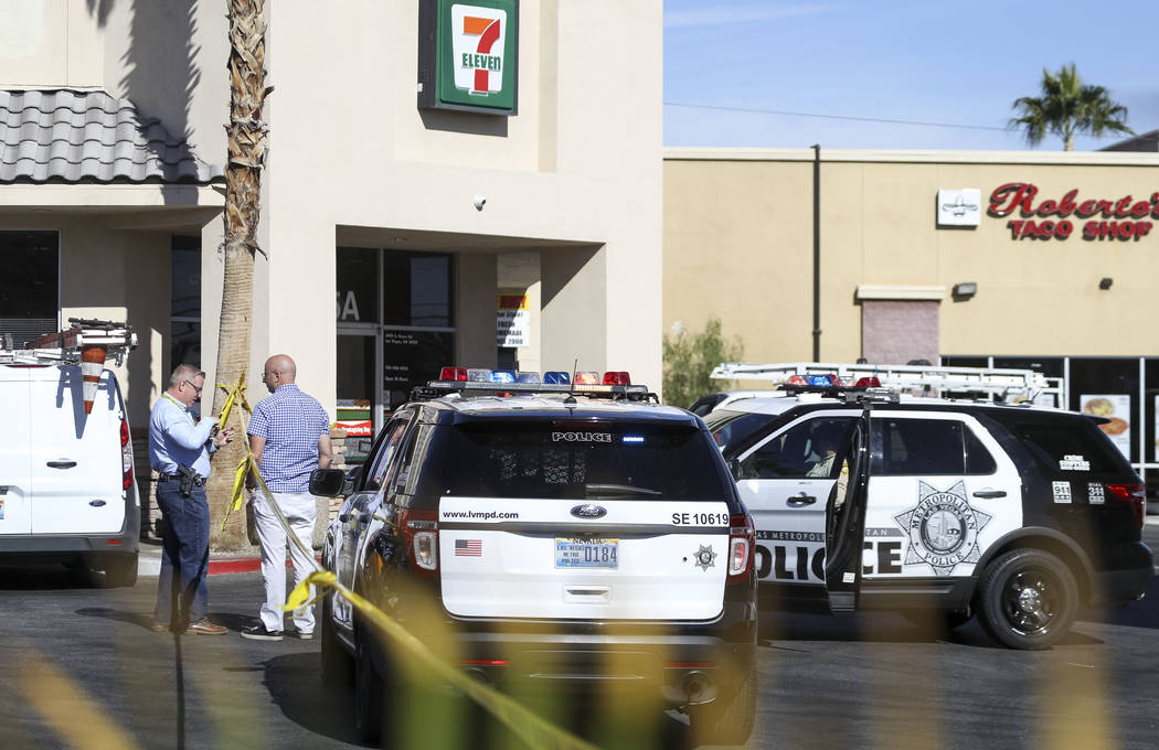 Las Vegas police and detectives investigate a shooting in the parking lot of a 7-Eleven store at the intersection of East Sunset and South Pecos roads in Las Vegas, Friday, Nov. 10, 2017. (Richard ...