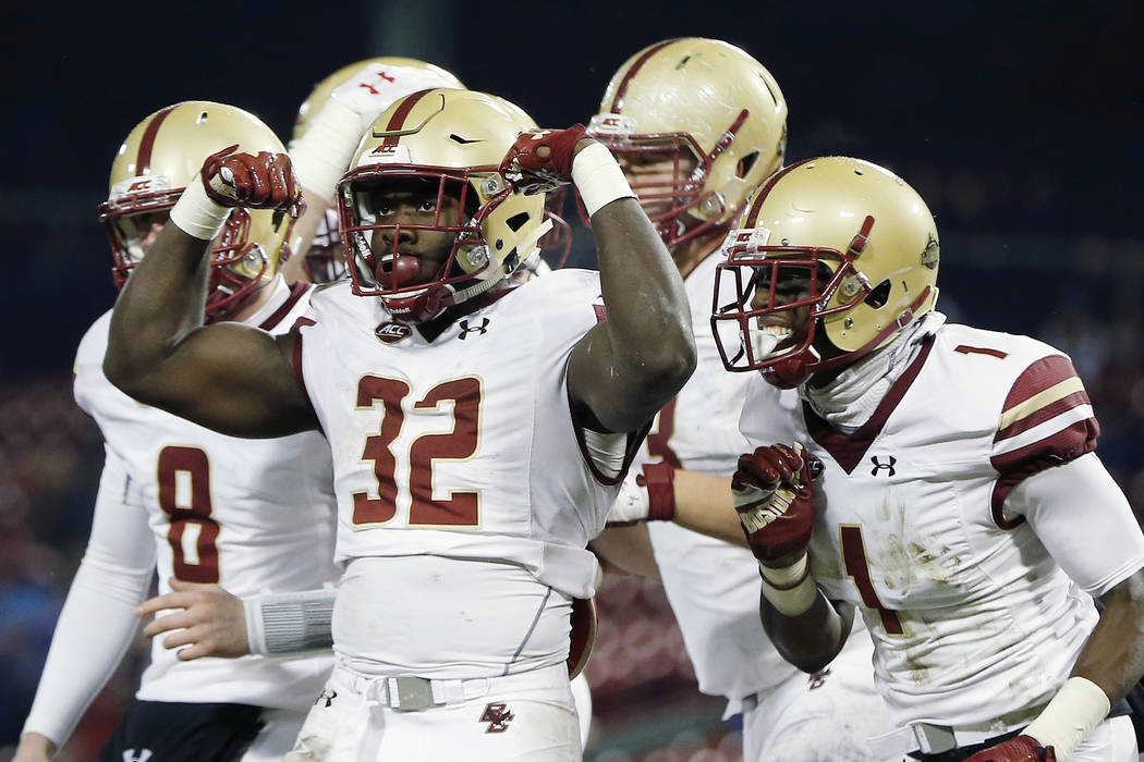 Boston College running back Jon Hilliman (32) celebrates his touchdown during the fourth quarter of an NCAA college football game against Connecticut at Fenway Park in Boston, Saturday, Nov. 18, 2 ...