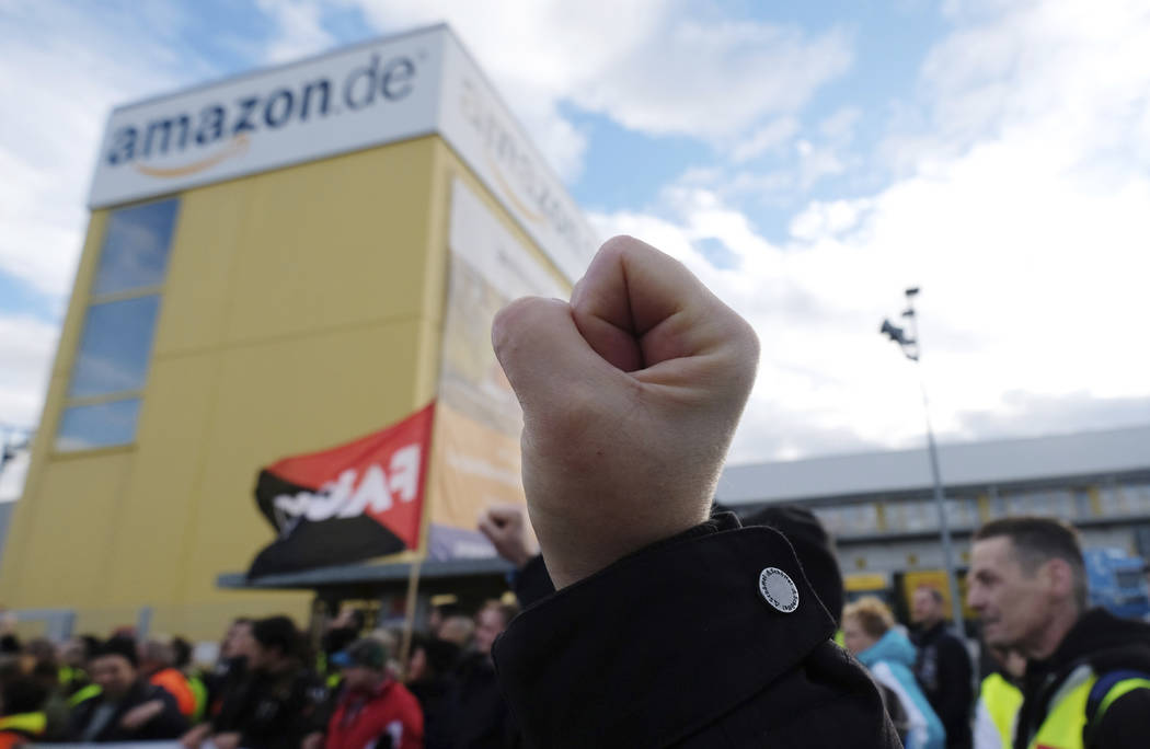 A participant of a demonstration raises his fist in front of the local site of the online retail company Amazon in Leipzig, Germany, Friday, Nov. 24 2017. A labor union says workers at a half doze ...