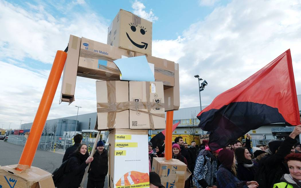 Participants of a demonstration during a strike hold up a figure made of cardboard in front of the local site of the online retail company Amazon in Leipzig, Germany, Friday, Nov. 24, 2017. A labo ...