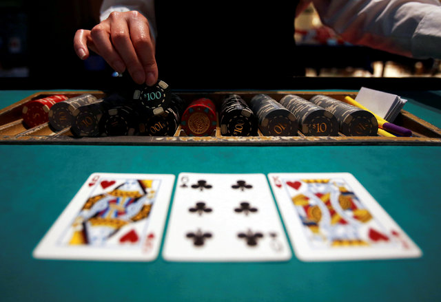 A dealer picks up chips on a mock black jack casino table during a photo opportunity at an international tourism promotion symposium in Tokyo, Japan September 28, 2013. (Yuya Shino/Reuters)
