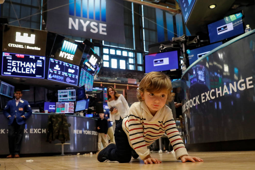 Hudson Maloney, son to specialist trader Gregg Maloney, crawls on the trading floor during a traditional bring-your-kids-to-work day at the New York Stock Exchange in New York, U.S., November 24,  ...