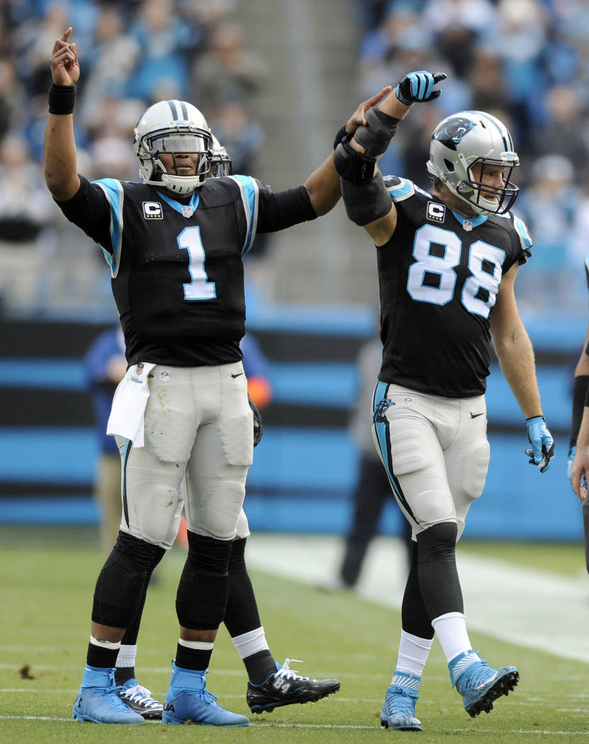 Carolina Panthers' Greg Olsen (88) celebrates with Cam Newton (1) after Olsen passed 1,000 yards receiving in the first half of an NFL football game against the Atlanta Falcons in Charlotte, N.C., ...